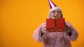 Εύθυμο ανώτερο θηλυκό στον αστείο ιματισμό που δίνει το δώρο γενεθλίων, εορτασμός φιλμ μικρού μήκους