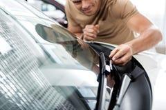 Εύθυμο αρσενικό που εξετάζει τον τεχνικό εξοπλισμό του αυτοκινήτου στοκ εικόνα με δικαίωμα ελεύθερης χρήσης