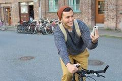 Εύθυμο αρσενικό που προσπαθεί να βρεί τις κατευθύνσεις στο έξυπνο τηλέφωνό του στοκ εικόνες με δικαίωμα ελεύθερης χρήσης