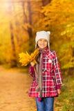 Εύθυμο ασιατικό κορίτσι με τη δέσμη των κίτρινων φύλλων Στοκ Φωτογραφία