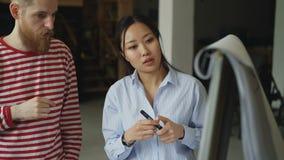 Εύθυμο ασιατικό κορίτσι που εξηγεί το πρόγραμμα ξεκινήματος για το flipchart στον άνδρα συνάδελφος hipster στο γραφείο σοφιτών απόθεμα βίντεο