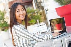Εύθυμο ασιατικό κορίτσι που χρησιμοποιεί ένα lap-top Στοκ Εικόνες
