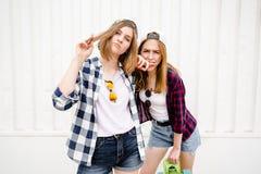Εύθυμο αστείο κορίτσι δύο που φορά τα ελεγμένα πουκάμισα που θέτουν ενάντια στον τοίχο οδών στην οδό στοκ εικόνες