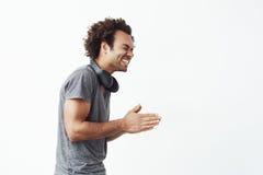 Εύθυμο αφρικανικό άτομο με το γέλιο ακουστικών που στέκεται στο σχεδιάγραμμα πέρα από το άσπρο υπόβαθρο Στοκ εικόνα με δικαίωμα ελεύθερης χρήσης
