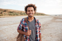 Εύθυμο αφρικανικό άτομο που στέκεται υπαίθρια και που κρατά το σακίδιο πλάτης Στοκ φωτογραφία με δικαίωμα ελεύθερης χρήσης