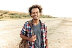 Εύθυμο αφρικανικό άτομο που στέκεται υπαίθρια και που κρατά το σακίδιο πλάτης Στοκ Εικόνα