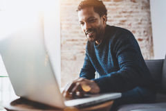 Εύθυμο αφρικανικό άτομο χρησιμοποιώντας τον υπολογιστή και χαμογελώντας καθμένος στον καναπέ Έννοια των νέων επιχειρηματιών που ε στοκ εικόνα
