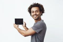 Εύθυμο αφρικανικό χαμόγελο ατόμων που εξετάζει τη κάμερα που παρουσιάζει κενή οθόνη ταμπλετών πέρα από τον άσπρο τοίχο Στοκ φωτογραφία με δικαίωμα ελεύθερης χρήσης