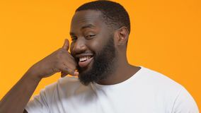 Εύθυμο αφροαμερικανός άτομο που παρουσιάζει σημάδι κλήσης, χειρονομία φλερτ, κινητή επικοινωνία απόθεμα βίντεο