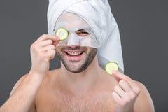 εύθυμο γενειοφόρο άτομο με τις φέτες μασκών και αγγουριών κολλαγόνων, Στοκ Εικόνες