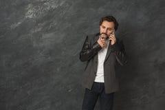 Εύθυμο γενειοφόρο άτομο που μιλά στο τηλέφωνο Στοκ Εικόνα