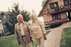 Εύθυμο γκρίζο μαλλιαρό ζευγάρι χαμόγελου που αντιμετωπίζει το σπίτι στοκ εικόνες