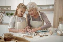 Εύθυμο εγγόνι που μαθαίνει να κάνει τη ζύμη στην κουζίνα Στοκ φωτογραφία με δικαίωμα ελεύθερης χρήσης