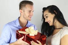 Εύθυμο ευτυχές ζεύγος που προσφέρει ένα παρόν Στοκ Φωτογραφίες