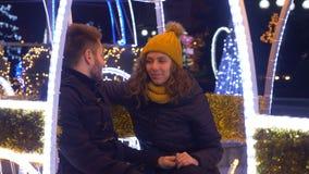 Εύθυμο ευτυχές νέο ζεύγος που έχει τη διασκέδαση στην έκθεση Χριστουγέννων απόθεμα βίντεο