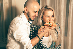 Εύθυμο ζεύγος ερωτευμένο έχοντας τη διασκέδαση με την πίτσα στο κόμμα Στοκ φωτογραφία με δικαίωμα ελεύθερης χρήσης