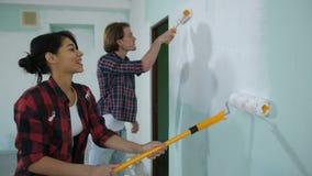 Εύθυμο ζεύγος που ανακαινίζει το σπίτι με το φρέσκο χρώμα απόθεμα βίντεο