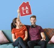 Εύθυμο ζεύγος που κρατά ένα εικονίδιο πώλησης σπιτιών στοκ φωτογραφία