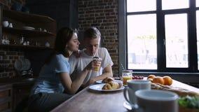 Εύθυμο ζεύγος που μοιράζεται το χυμό από πορτοκάλι στην κουζίνα φιλμ μικρού μήκους