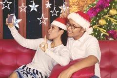 Εύθυμο ζεύγος που παίρνει την εικόνα με τις διακοσμήσεις Χριστουγέννων Στοκ Φωτογραφίες
