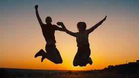 Εύθυμο ζεύγος που πηδά στο ηλιοβασίλεμα απόθεμα βίντεο
