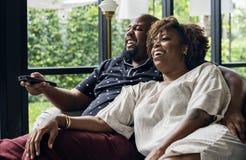 Εύθυμο ζεύγος που προσέχει τη TV από κοινού στοκ φωτογραφία