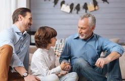 Εύθυμο θετικό άτομο που τινάζει το χέρι εγγονών του στοκ εικόνες