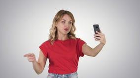 Εύθυμο θηλυκό βίντεο καταγραφής blogger στην μπροστινή κάμερα του σύγχρονου τηλεφώνου περπατώντας στο υπόβαθρο κλίσης φιλμ μικρού μήκους