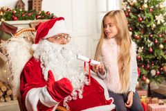 Εύθυμο θηλυκό παιδί που μιλά με Άγιο Βασίλη Στοκ φωτογραφία με δικαίωμα ελεύθερης χρήσης