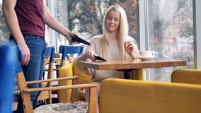 Εύθυμο θηλυκό στον καφέ που κάνει τη σε απευθείας σύνδεση πληρωμή που χρησιμοποιεί το smartphone 4K φιλμ μικρού μήκους