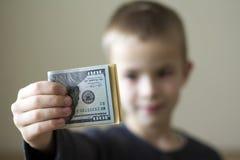 Εύθυμο θολωμένο αγόρι που παρουσιάζει αμερικανικά χρήματα δολαρίων στοκ φωτογραφίες με δικαίωμα ελεύθερης χρήσης
