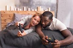 Εύθυμο διεθνές ζεύγος που παίζει τα τηλεοπτικά παιχνίδια στο σπίτι Στοκ εικόνα με δικαίωμα ελεύθερης χρήσης