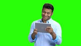 Εύθυμο ινδικό άτομο με το PC ταμπλετών στην πράσινη οθόνη απόθεμα βίντεο