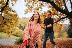 Εύθυμο και θετικό νέο πάρκο γυναικών runthrough Κρατά το χέρι του Ο τύπος την ακολουθεί Η γυναίκα Youn ανατρέχει στοκ φωτογραφία