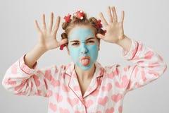 Εύθυμο και παιδαριώδες χαριτωμένο κορίτσι στην του προσώπου μάσκα και τρίχα-ρόλερ, που φορούν nightwear με την τυπωμένη ύλη καρδι στοκ εικόνα με δικαίωμα ελεύθερης χρήσης