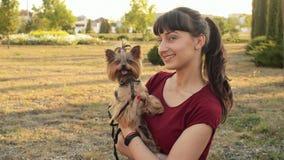 Εύθυμο καυκάσιο κορίτσι και μικρή τοποθέτηση τεριέ του Γιορκσάιρ σκυλιών υπαίθρια στο πάρκο φιλμ μικρού μήκους
