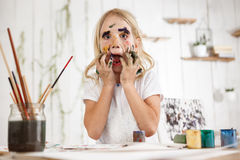 Εύθυμο καυκάσιο κορίτσι που έχει τη διασκέδαση με τα σημεία του χρώματος στο πρόσωπο και το ανοιγμένο στόμα της, σχετικά με το πρ στοκ εικόνες