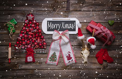 Εύθυμο κείμενο Χριστουγέννων στο ξύλινο σημάδι με τις κλασικές κόκκινες ευπρέπειες Χριστουγέννων Στοκ φωτογραφία με δικαίωμα ελεύθερης χρήσης