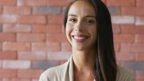 Εύθυμο κομψό brunette κοντά στο τουβλότοιχο απόθεμα βίντεο