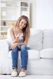 Εύθυμο κορίτσι με έναν τηλεχειρισμό για τη TV στοκ εικόνες με δικαίωμα ελεύθερης χρήσης