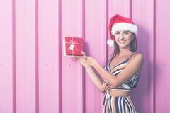 Εύθυμο κορίτσι με το καπέλο santa που παρουσιάζει κιβώτιο δώρων στο ρόδινο υπόβαθρο κρητιδογραφιών Έννοια Χριστουγέννων στοκ φωτογραφίες