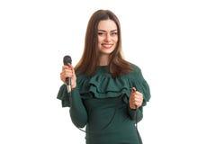 Εύθυμο κορίτσι με το μικρόφωνο στο πράσινο φόρεμα Στοκ Φωτογραφία