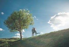 Εύθυμο κορίτσι με το νεαρό άνδρα από το δέντρο στοκ φωτογραφία με δικαίωμα ελεύθερης χρήσης