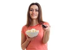 Εύθυμο κορίτσι με pop-corn που προσέχει μια TV Στοκ εικόνες με δικαίωμα ελεύθερης χρήσης
