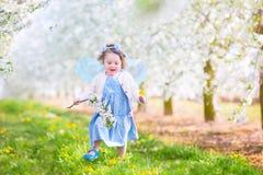 Εύθυμο κορίτσι μικρών παιδιών στο κοστούμι νεράιδων στον ανθίζοντας κήπο Στοκ Εικόνες