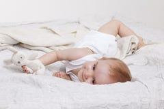 Εύθυμο κορίτσι μικρών παιδιών στο κρεβάτι Στοκ φωτογραφία με δικαίωμα ελεύθερης χρήσης