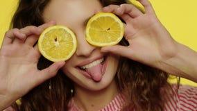 Εύθυμο κορίτσι που έχει τη διασκέδαση με τις φέτες λεμονιών στο κίτρινο υπόβαθρο εύθυμη γυναίκα φιλμ μικρού μήκους