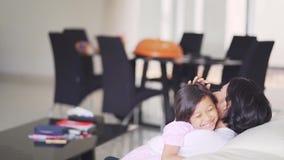 Εύθυμο κορίτσι που αγκαλιάζει τη μητέρα της στο σπίτι φιλμ μικρού μήκους