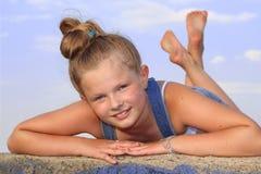 Εύθυμο κορίτσι που βρίσκεται στο στομάχι της Στοκ Φωτογραφία