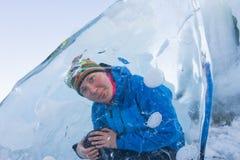 Εύθυμο κορίτσι που κοιτάζει μέσω του διαφανούς επιπλέοντος πάγου πάγου στη λίμνη Β Στοκ Φωτογραφία